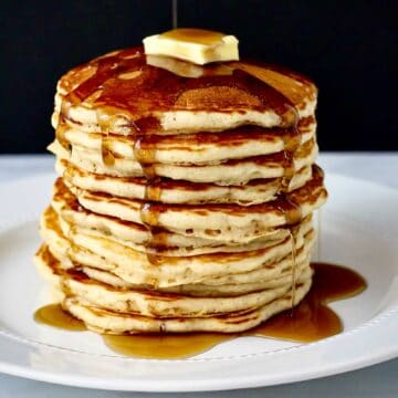 Side view of a tall stack of pancakes drizzled with maple syrup set against a black background.