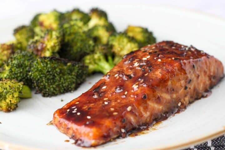 The glazed salmon is shown on a dish with a serving of roasted broccoli.