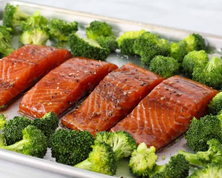 Marinated Soy Ginger Salmon is shown on a sheet pan surrounded by broccoli prior to baking.