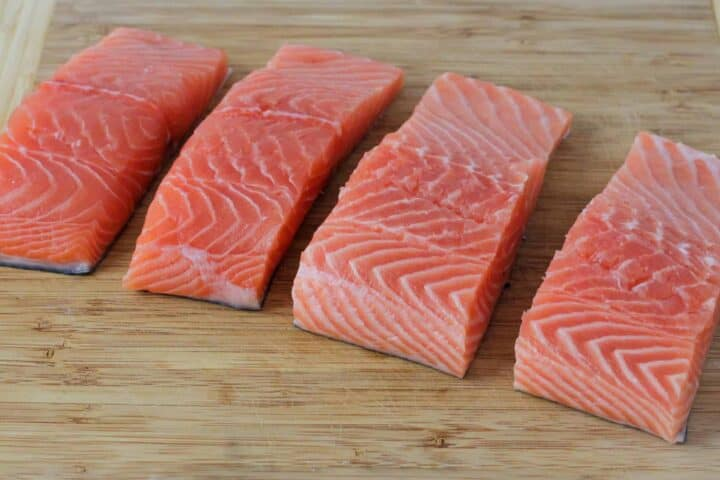 Salmon filets shown on a cutting board cut into individual serving sizes to allow the marinade to penetrate all sides of the salmon.