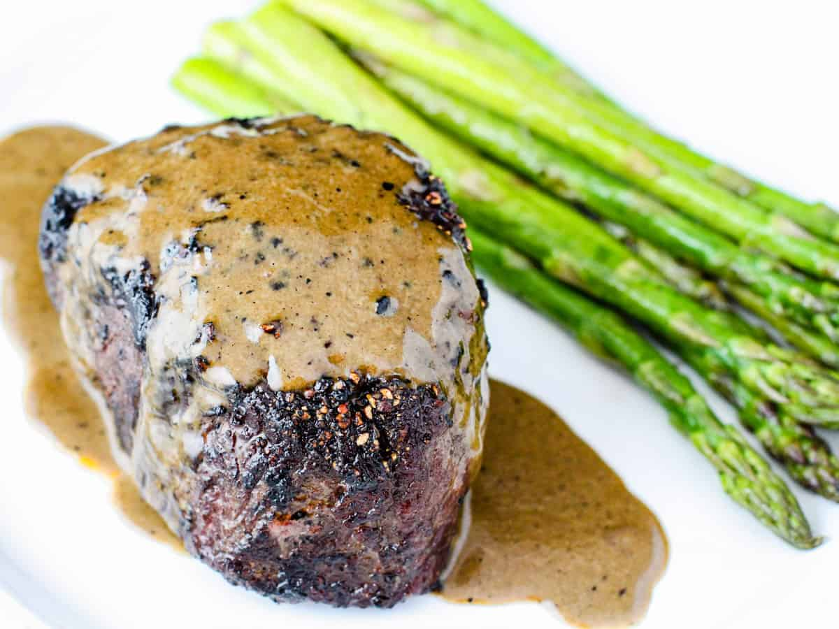 Overhead angle view of a steak covered is a creamy au poivre sauce.