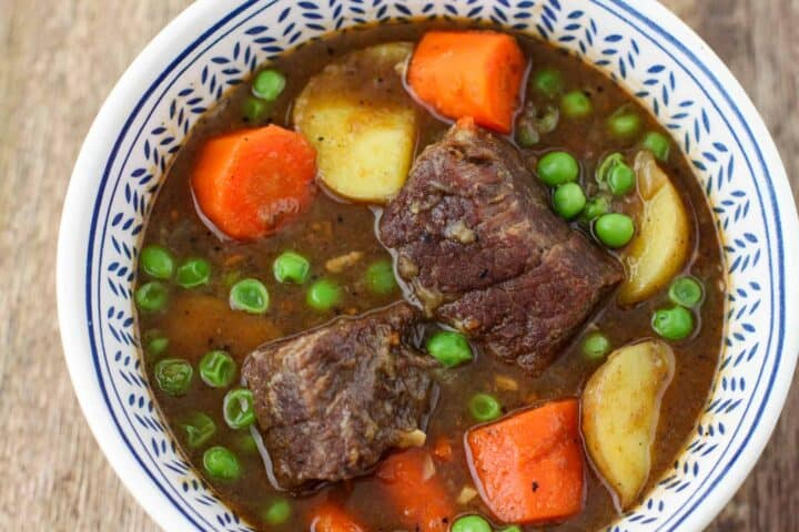 A bowl full of chunky beef stew with carrots, potatoes, and peas.