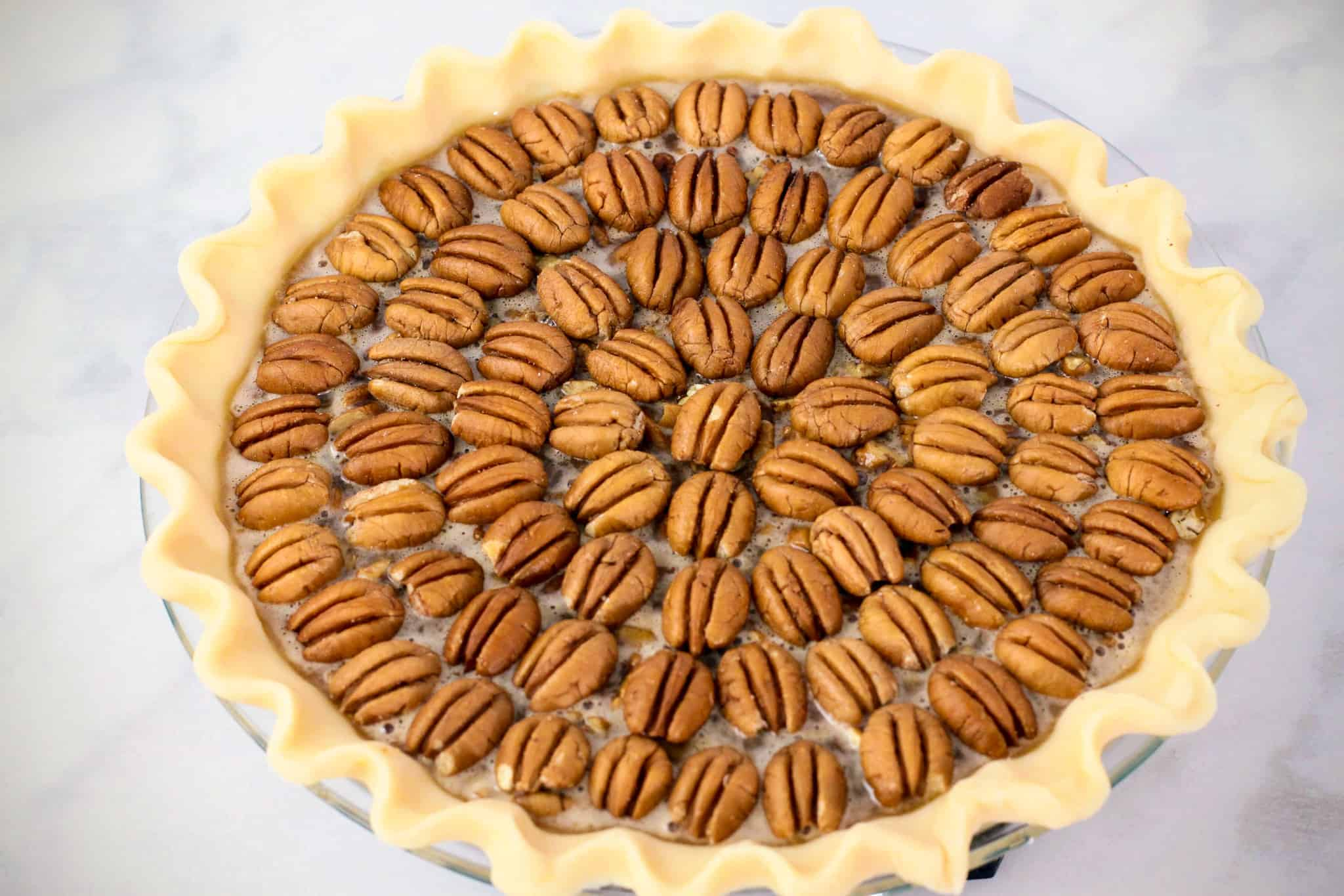 Side angle view of a prepared pecan pie with the pecan topping arranged in a concentric circle pattern.