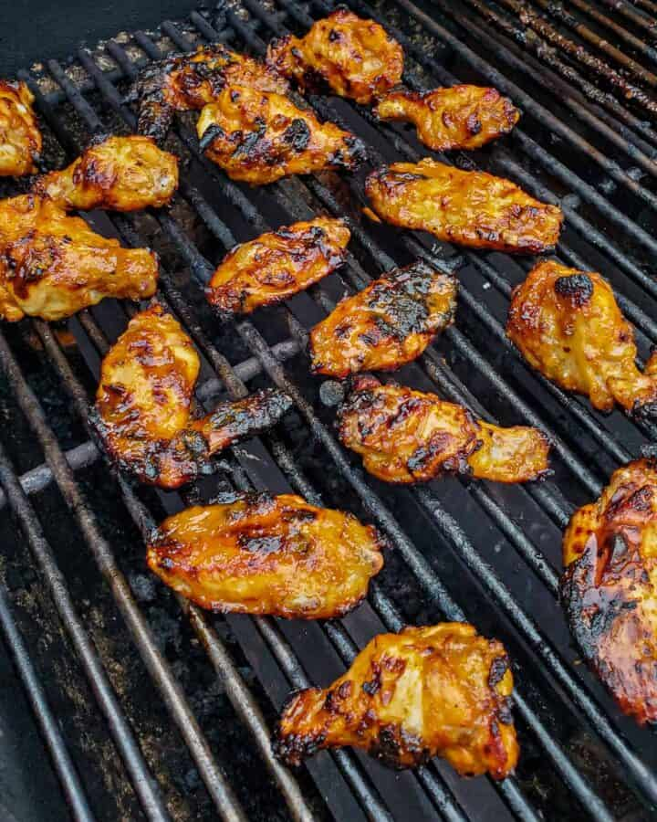 Chicken wings being cooked on a grill.