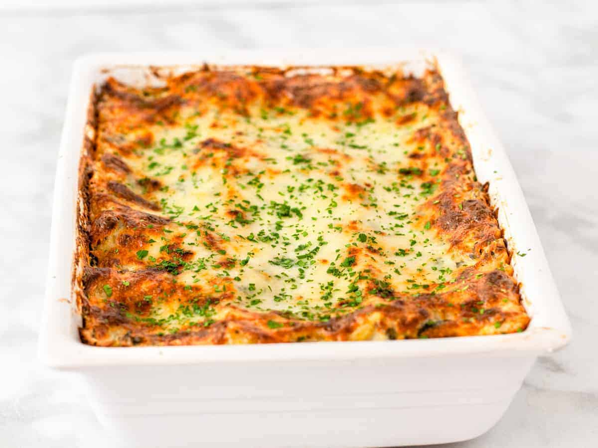 The baked lasagna is shown cooling on a countertop.