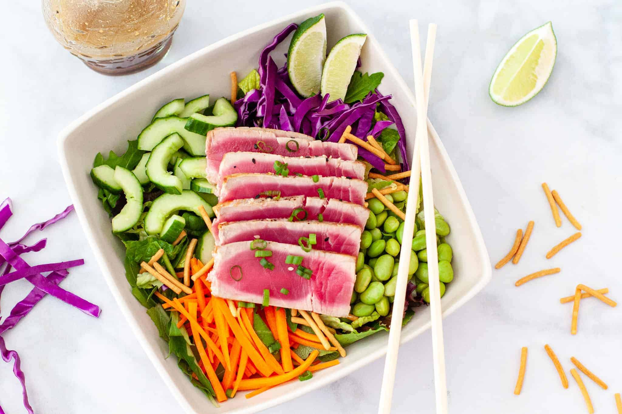 Overhead image of a bowl of salad topped with sliced seared tuna.