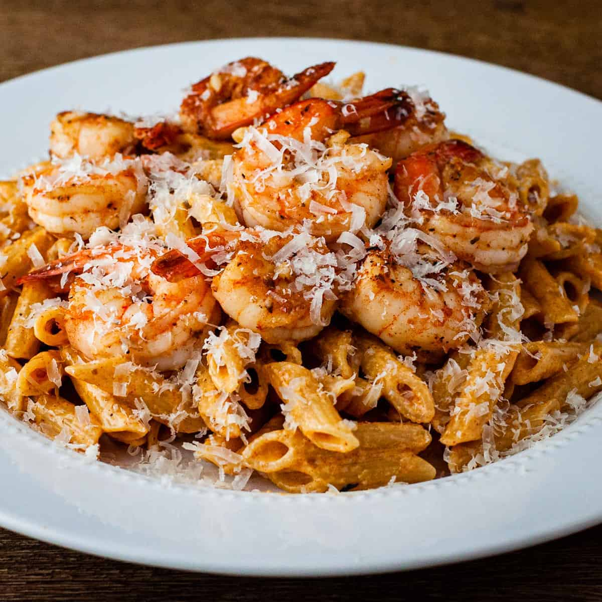 Side angle view of a large plate of creamy Cajun pasta topped with shrimp and grated parmesan cheese.