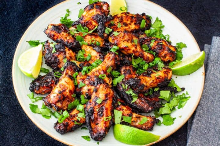 Grilled Chili Lime Chicken Wings served on a platter with lime wedges and scallions.