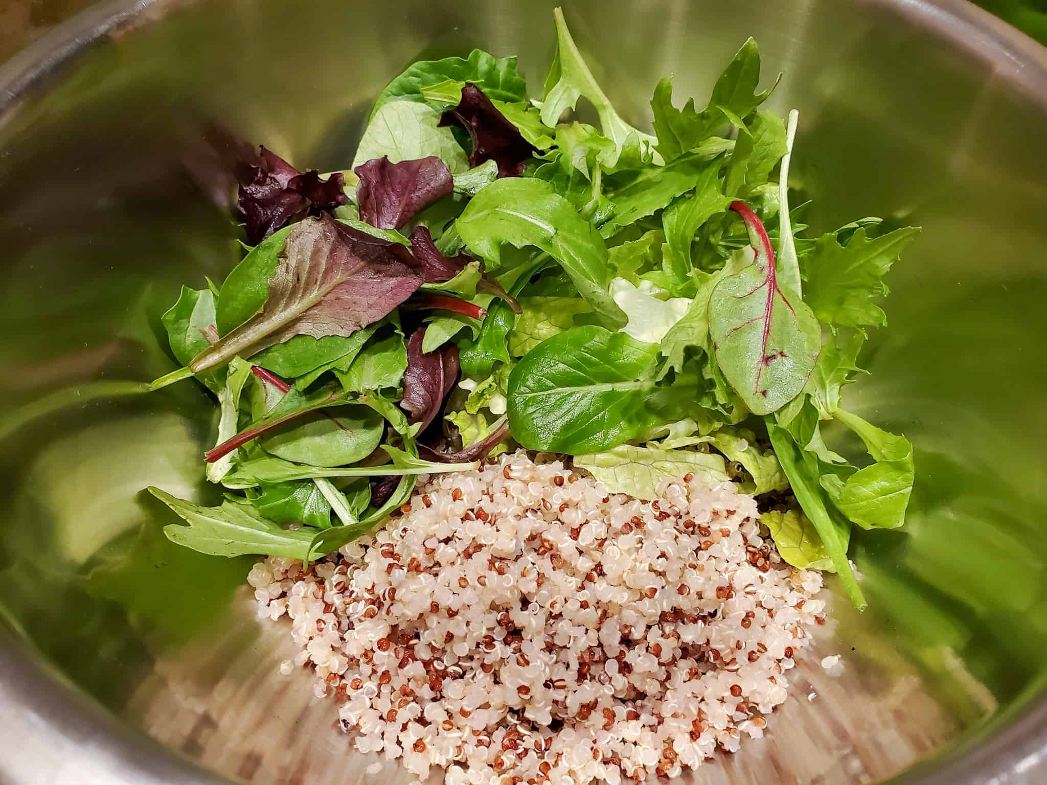 Quinoa and salad greens shown in a mixing bowl.