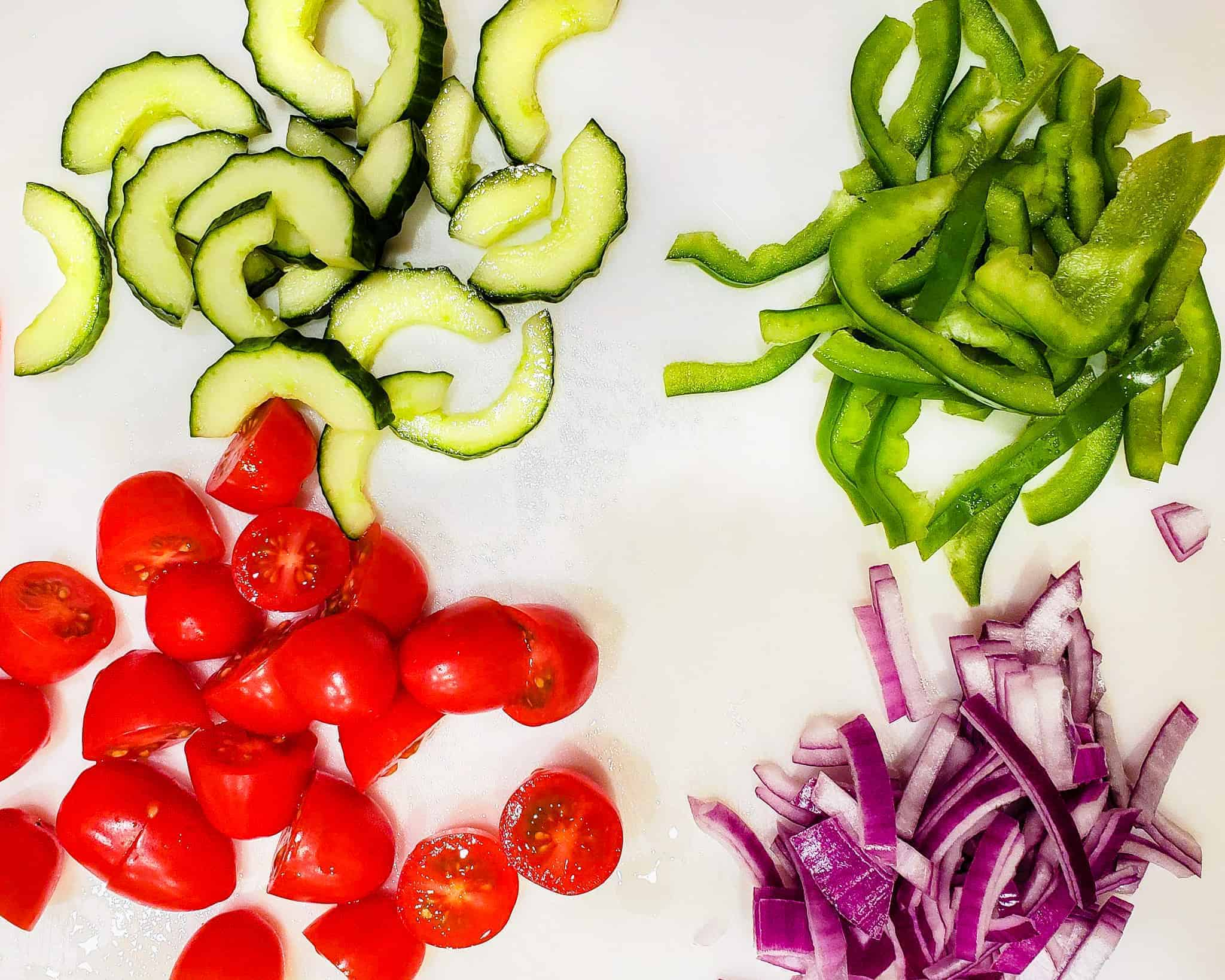 Sliced cucumber, green pepper, tomatoes, and red onion shown on a cutting board.