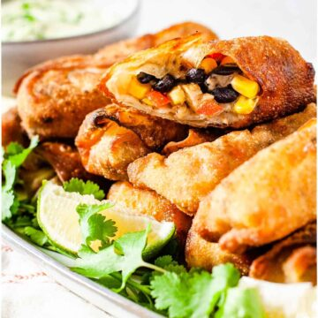 Southwestern chicken egg rolls served on a platter with creamy avocado dip and lime wedges.