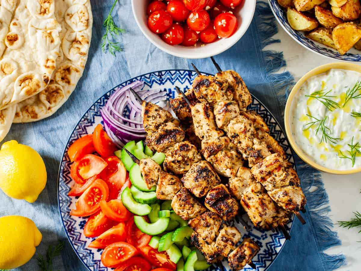 chicken souvlaki platter on table with sides