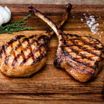 Grilled pork chops shown on a wood cutting board.
