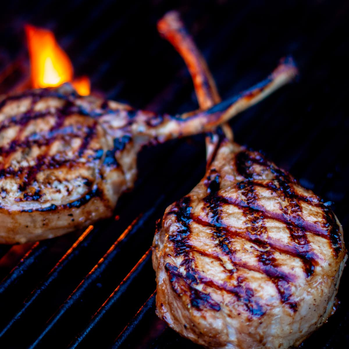 Pork chops shown being grilled over hot flames.
