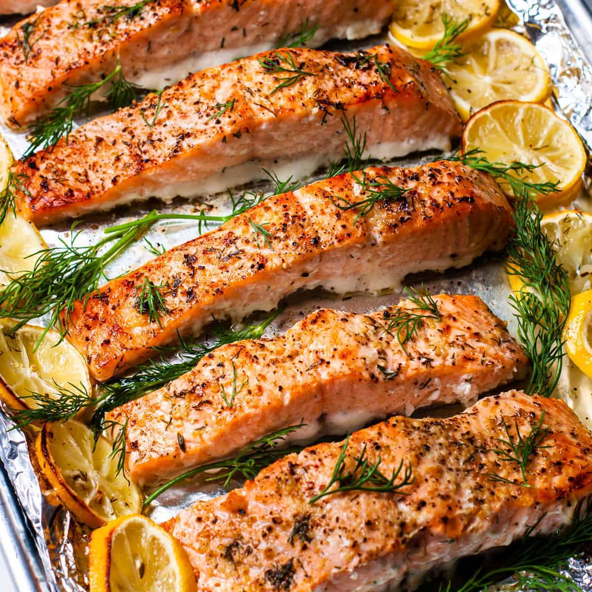 Side angle view of the lemon dill salmon surrounded by roasted lemon slices and fresh dill.
