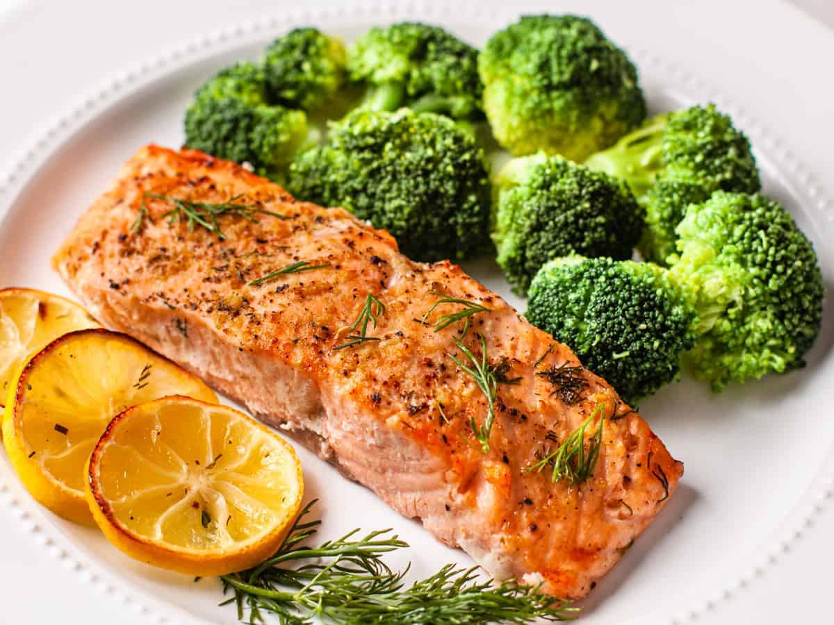 The finished lemon dill salmon served on plate with a side of steamed broccoli.