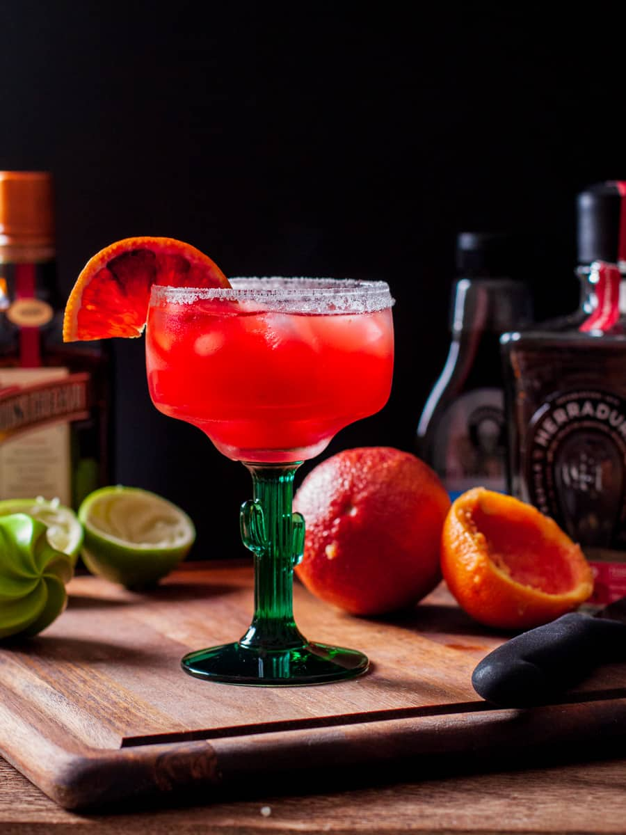 Margarita served in a sugar rimmed glass shown on cutting board with cut oranges and lime.
