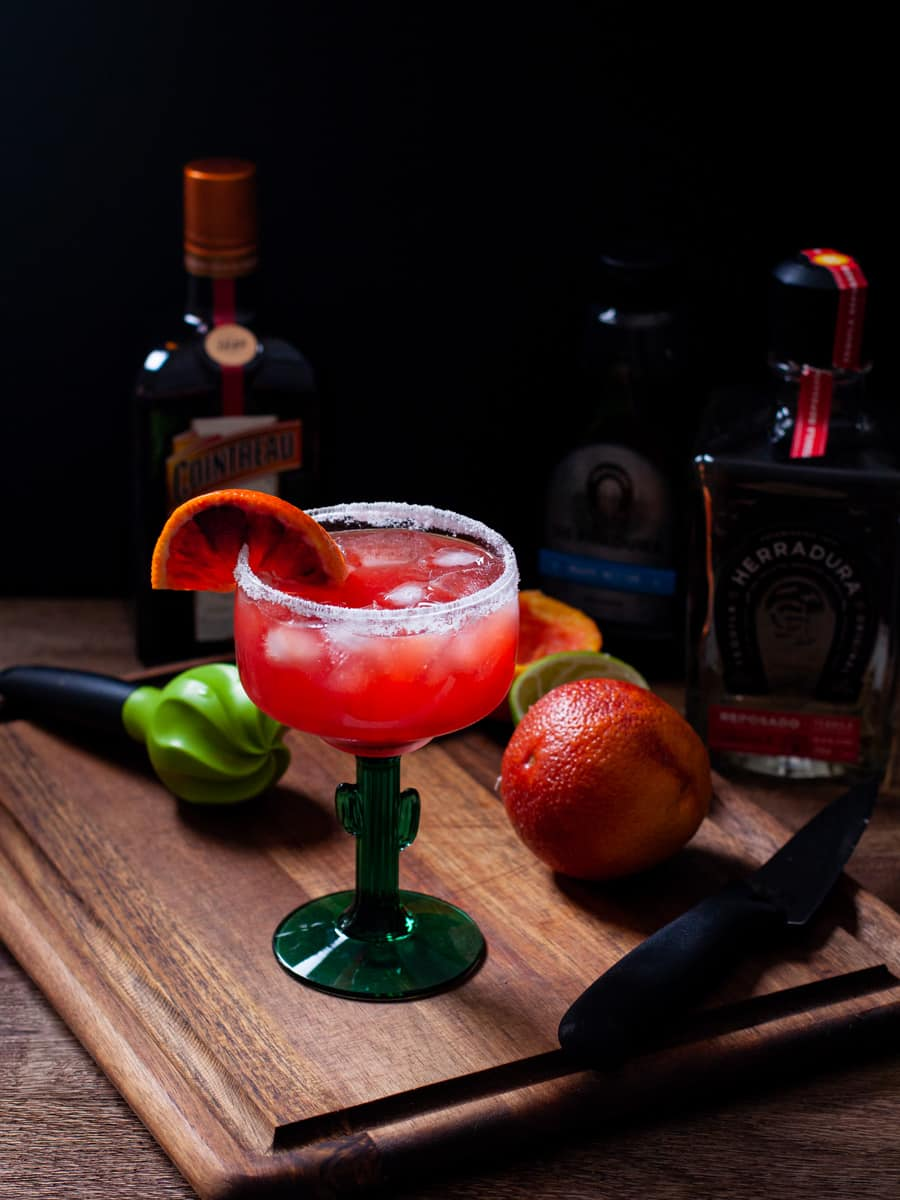 Margarita shown with fresh oranges and limes along with tequila bottle