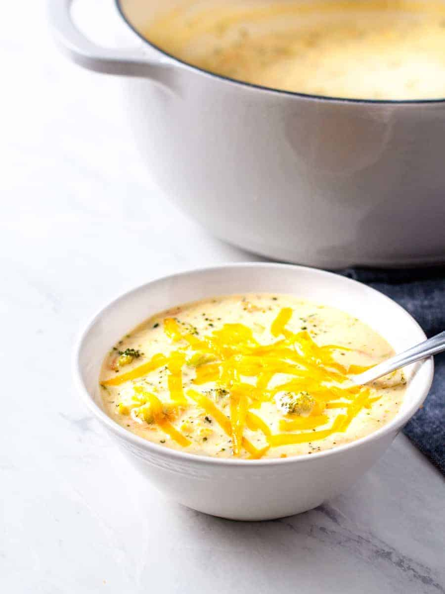 A bowl of broccoli cheese soup topped with grated cheddar cheese.