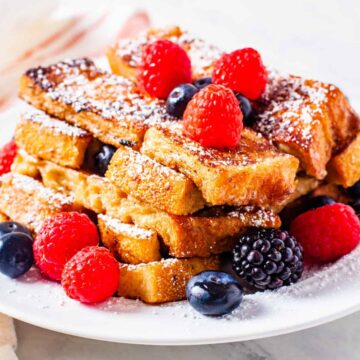 French toast sticks served on a plate topped with powdered sugar and fresh berries