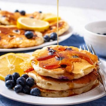 Lemon Blueberry pancakes shown with a drizzle of maple syrup