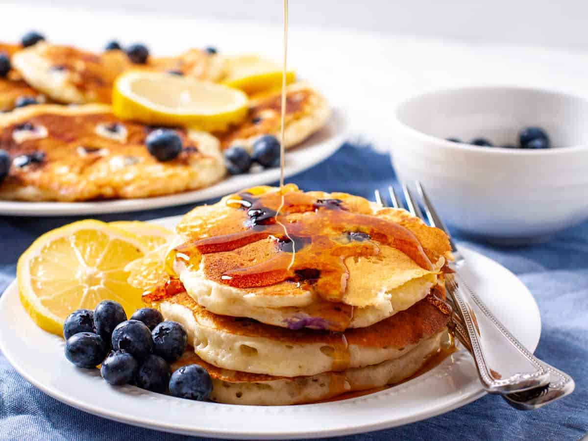 A plate of fluffy lemon blueberry pancakes with a drizzle of warm maple syrup