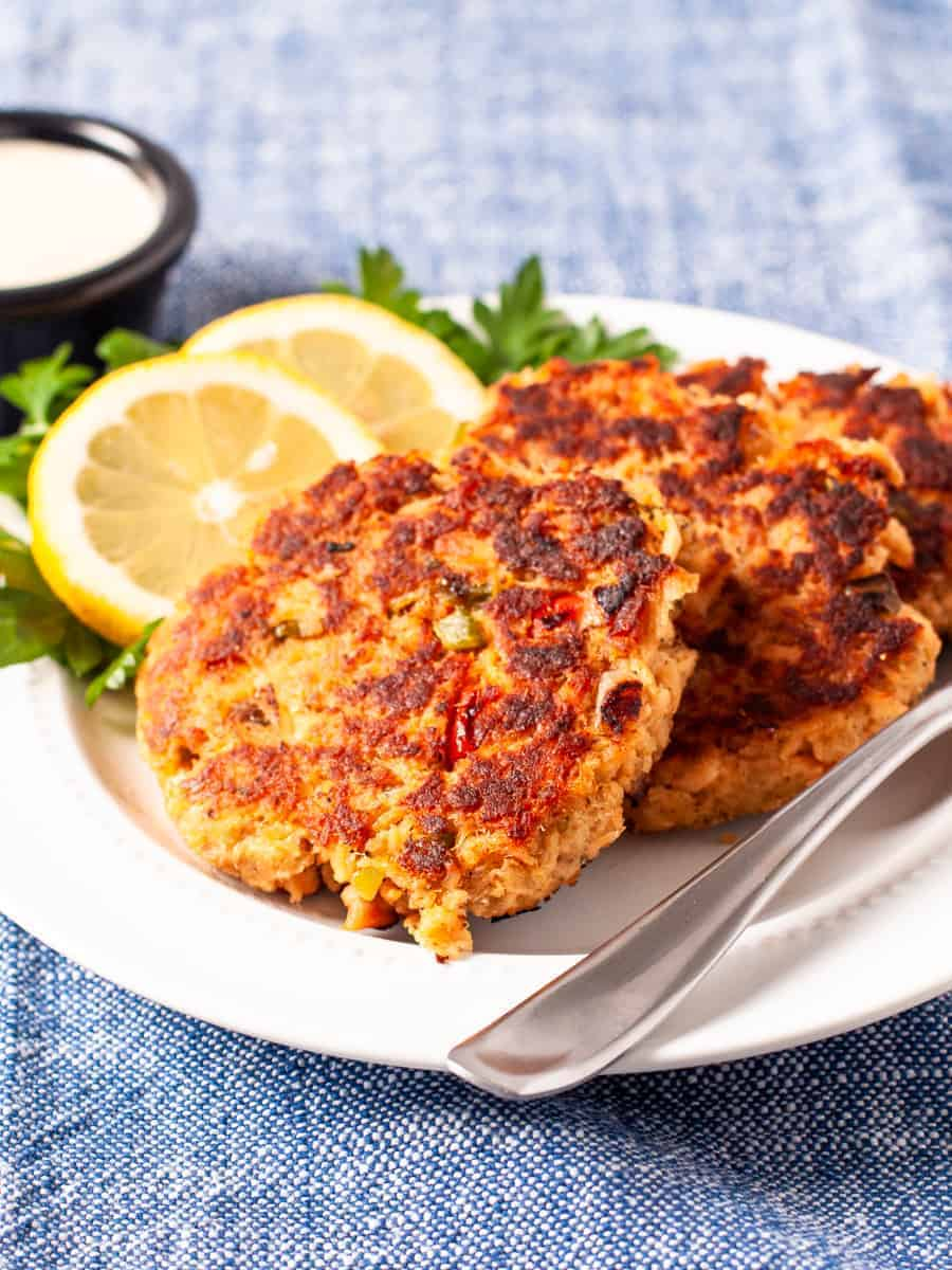 Golden brown salmon cakes served with dipping sauce and a garnish of fresh lemon slices and parsley.