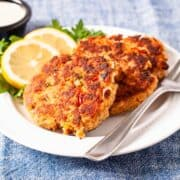 Golden brown salmon cakes served on a plate with fresh sliced lemon and dipping sauce