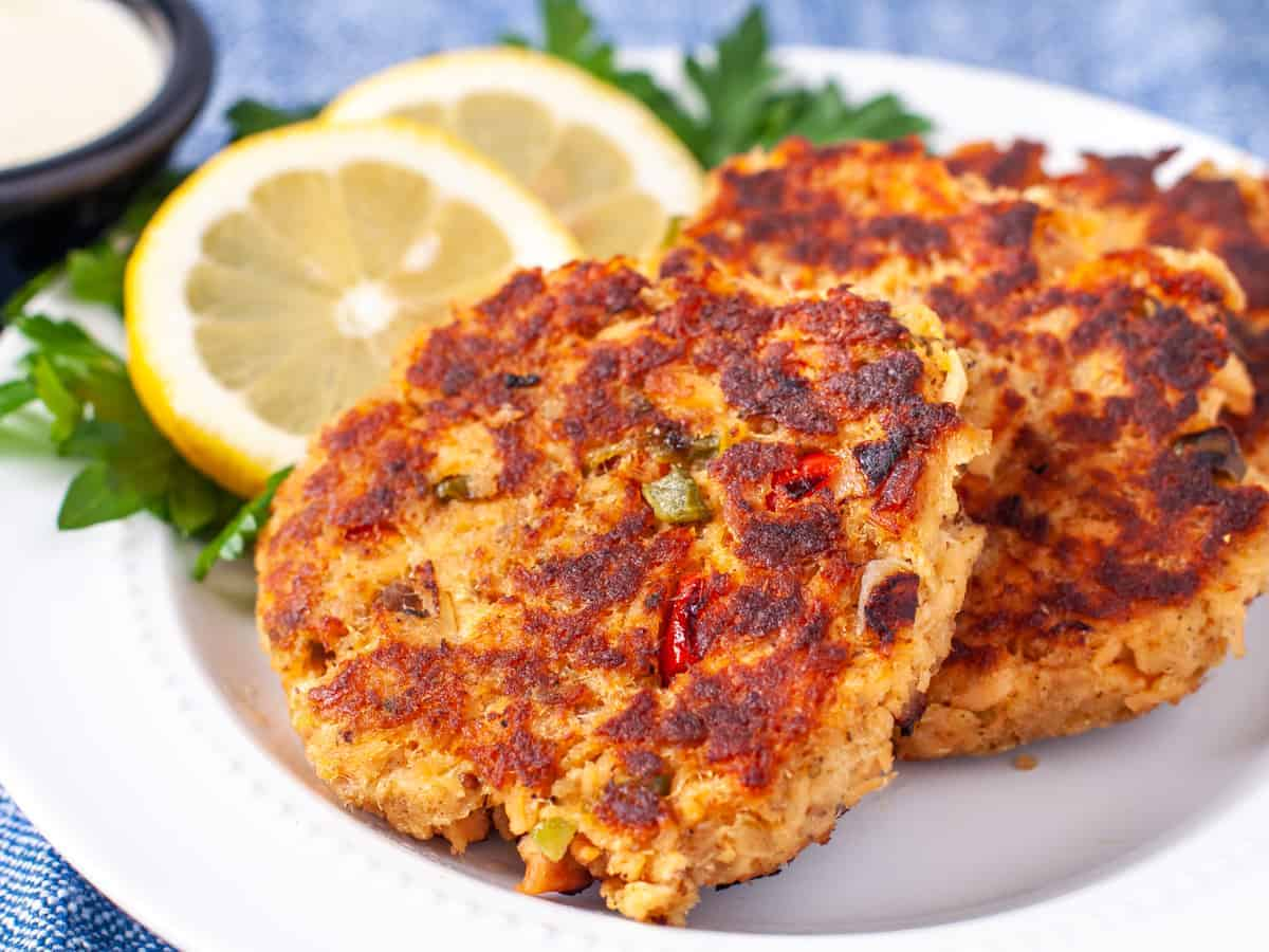 Close up shot of finished salmon cakes on a plate with fresh sliced lemon and parsley garnish.