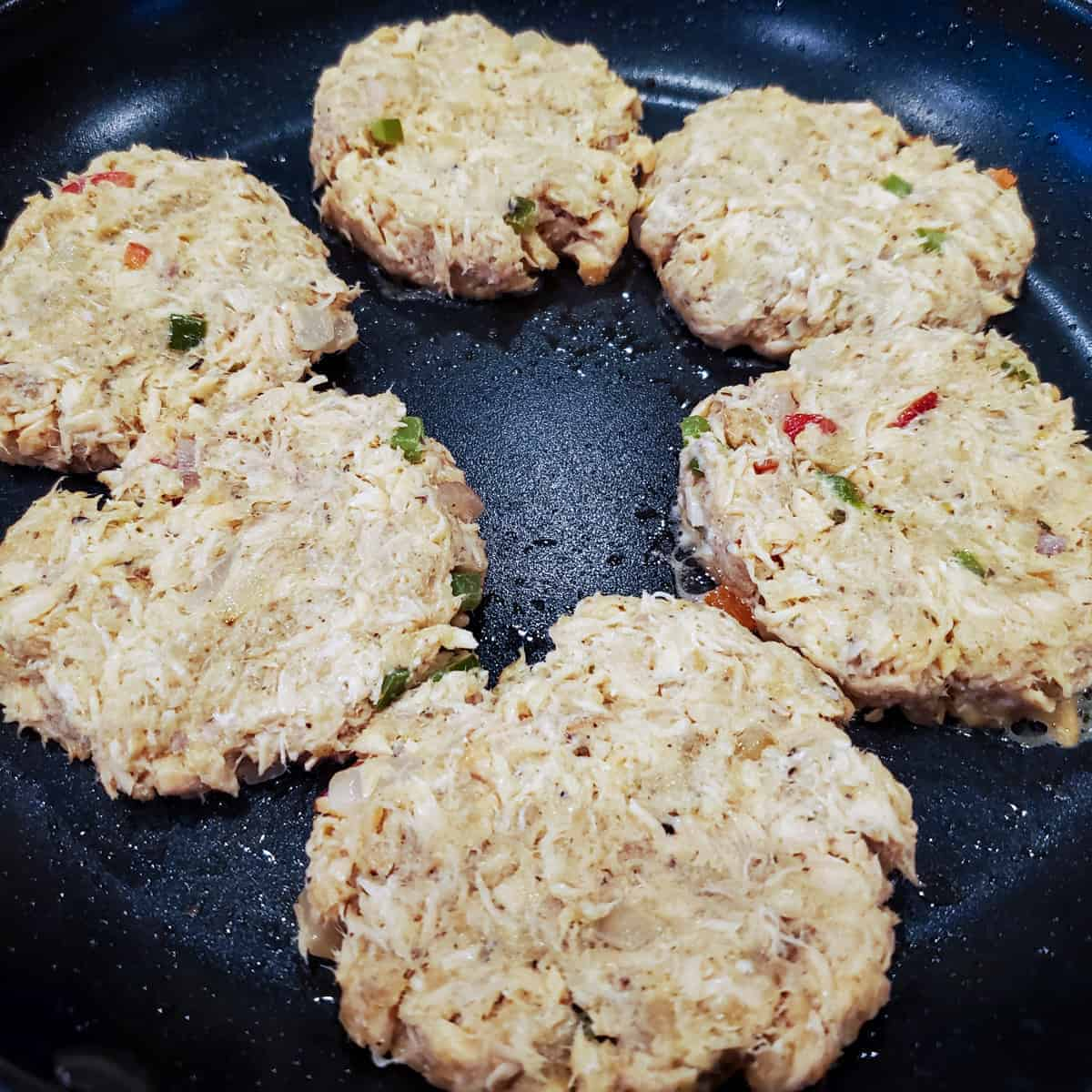 Salmon cake patties shown cooking in a large non-stick skillet
