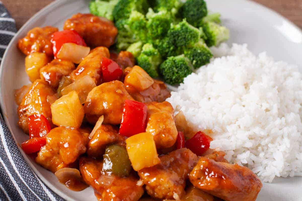 Finished plate of crispy golden brown sweet and sour chicken served with rice and broccoli.