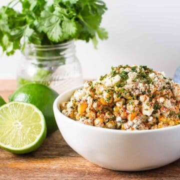 Mexican street corn salad in a serving bowl aong with fresh sliced limes and a jar with a bunch of fresh cilantro
