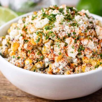 close up shot of Mexican street corn salad in a serving bowl topped with fresh chopped cilantro, cojita cheese, and chili powder