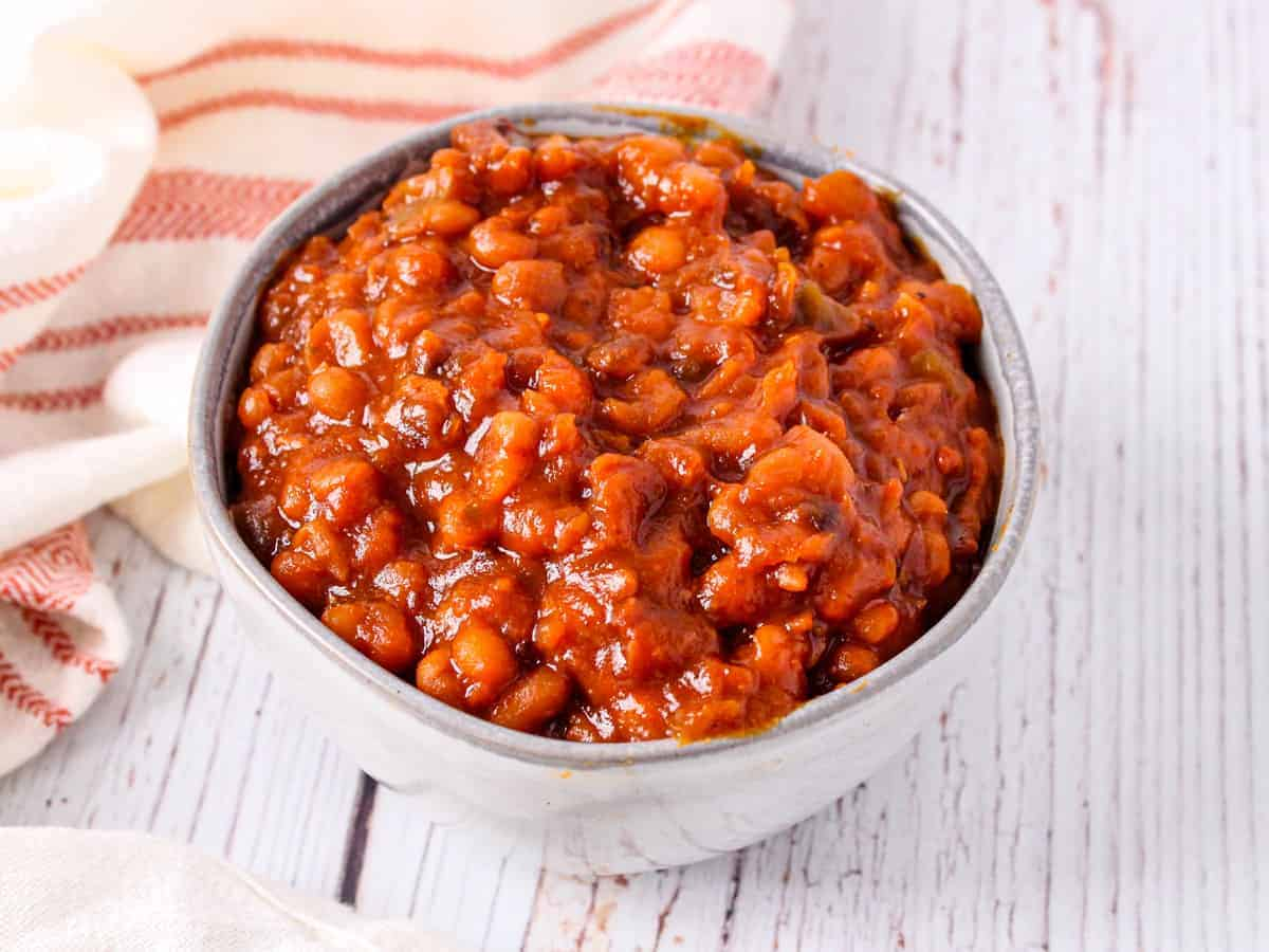 Image of the finished bowl of baked beans shown on a white wooden background.