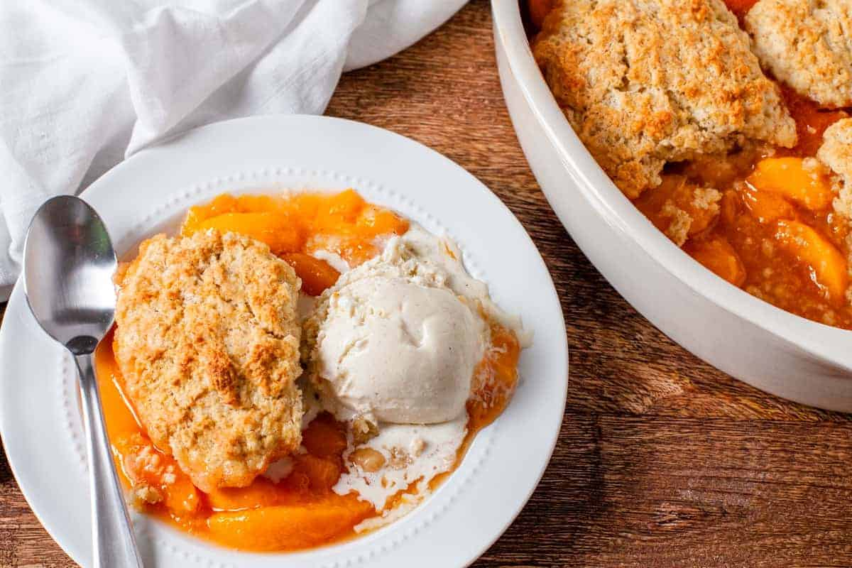 The finished cobbler is shown served on a plate with a scoop of vanilla ice cream.