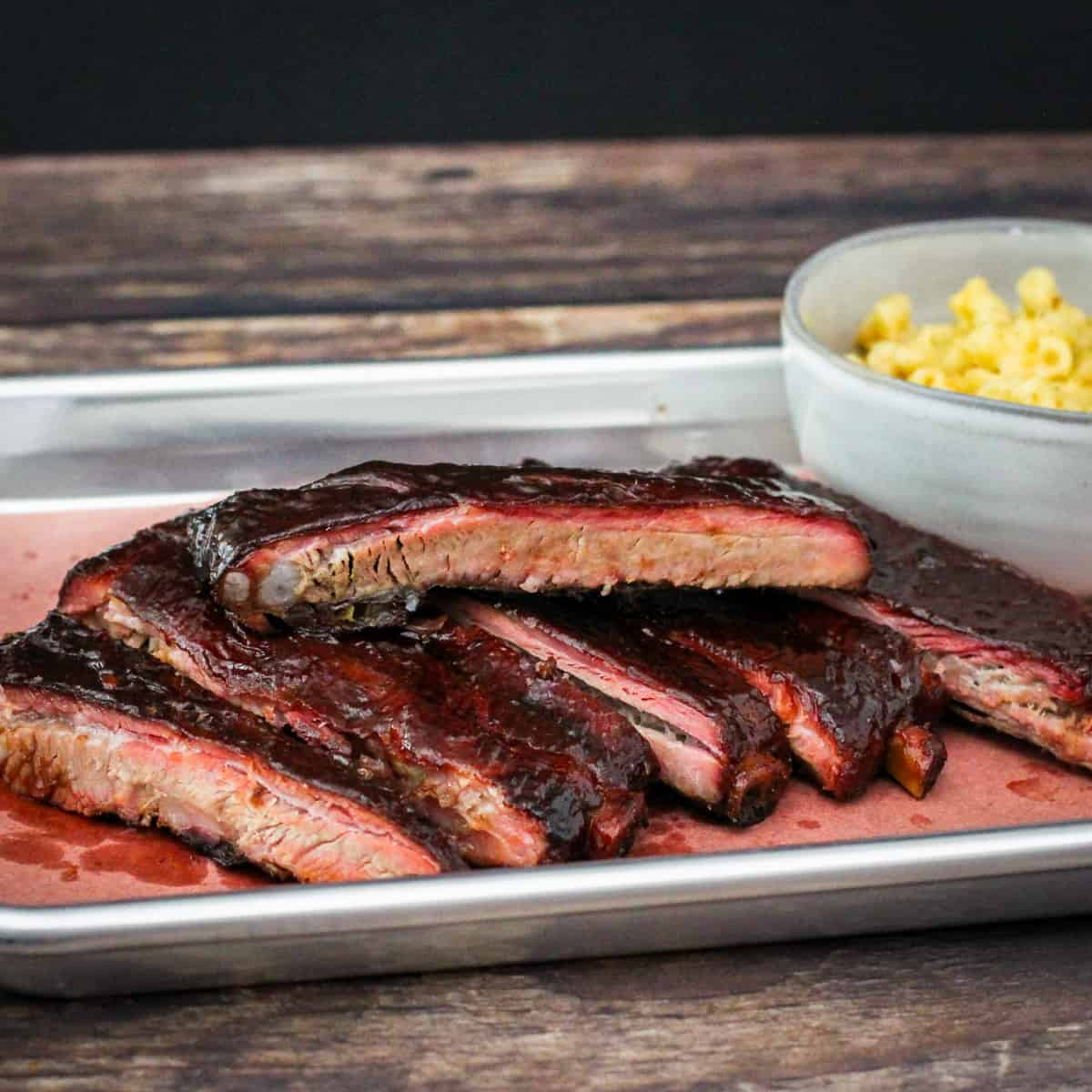 The finished spareribs are shown sliced and served on a platter with a bowl of mac and cheese.