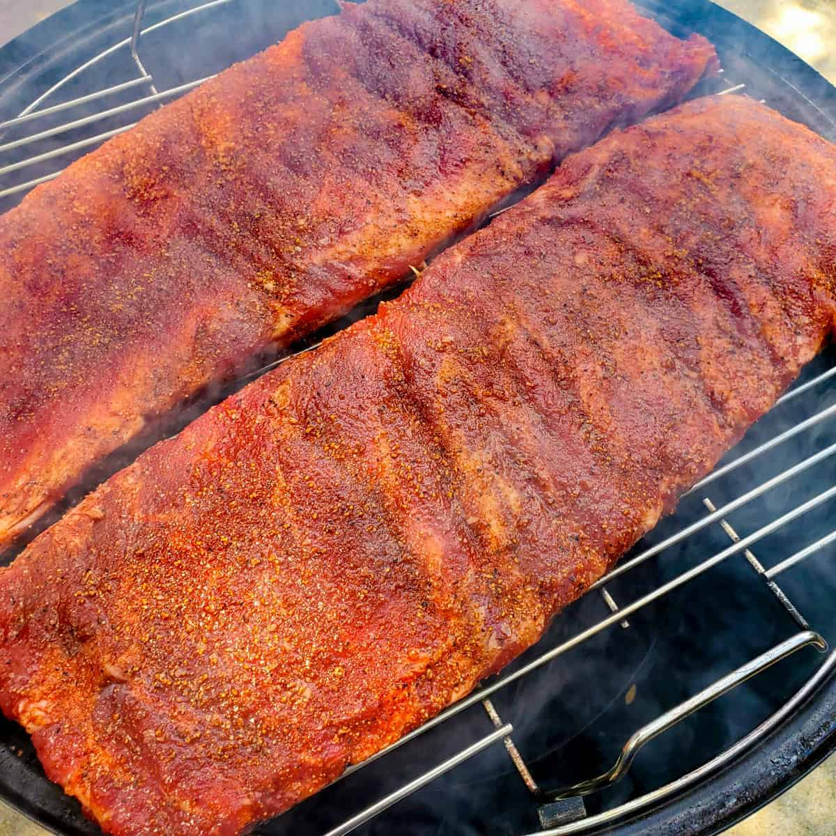 Seasoned spareribs shown on a smoker at the start of cooking