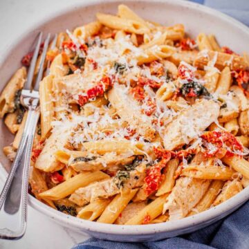A large bowl of Tuscan chicken pasta with spinach and sun dried tomatoes in a creamy sauce topped with grated Parmesan cheese.