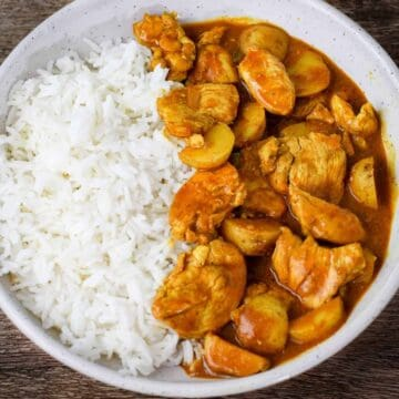 Overhead shot of yellow curry chicken and potatoes served with steamed rice