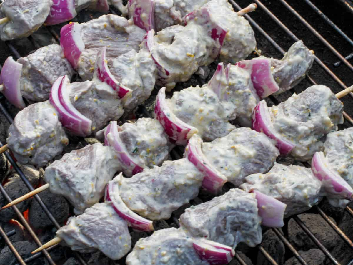 Marinated lamb kebabs cooking on a hot grill.