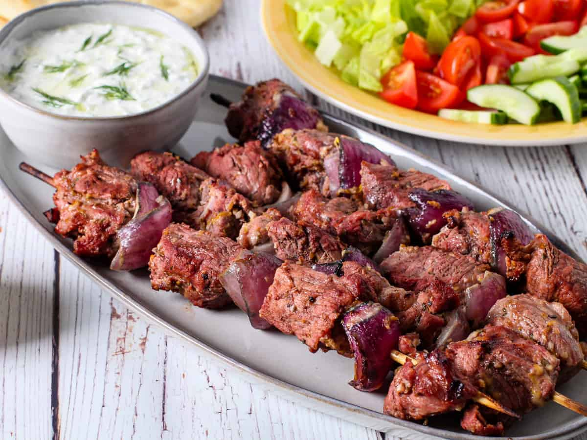 Greek yogurt marinated lamb kebabs shown served on a platter with a bowl of tzatziki sauce and fresh vegetables.