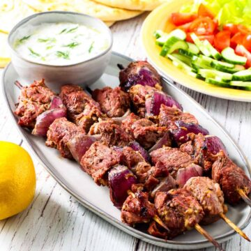 Grilled lamb kebabs served with warm pita bread, a bowl of fresh tzatziki sauce, and fresh tomatoes and cucumbers.