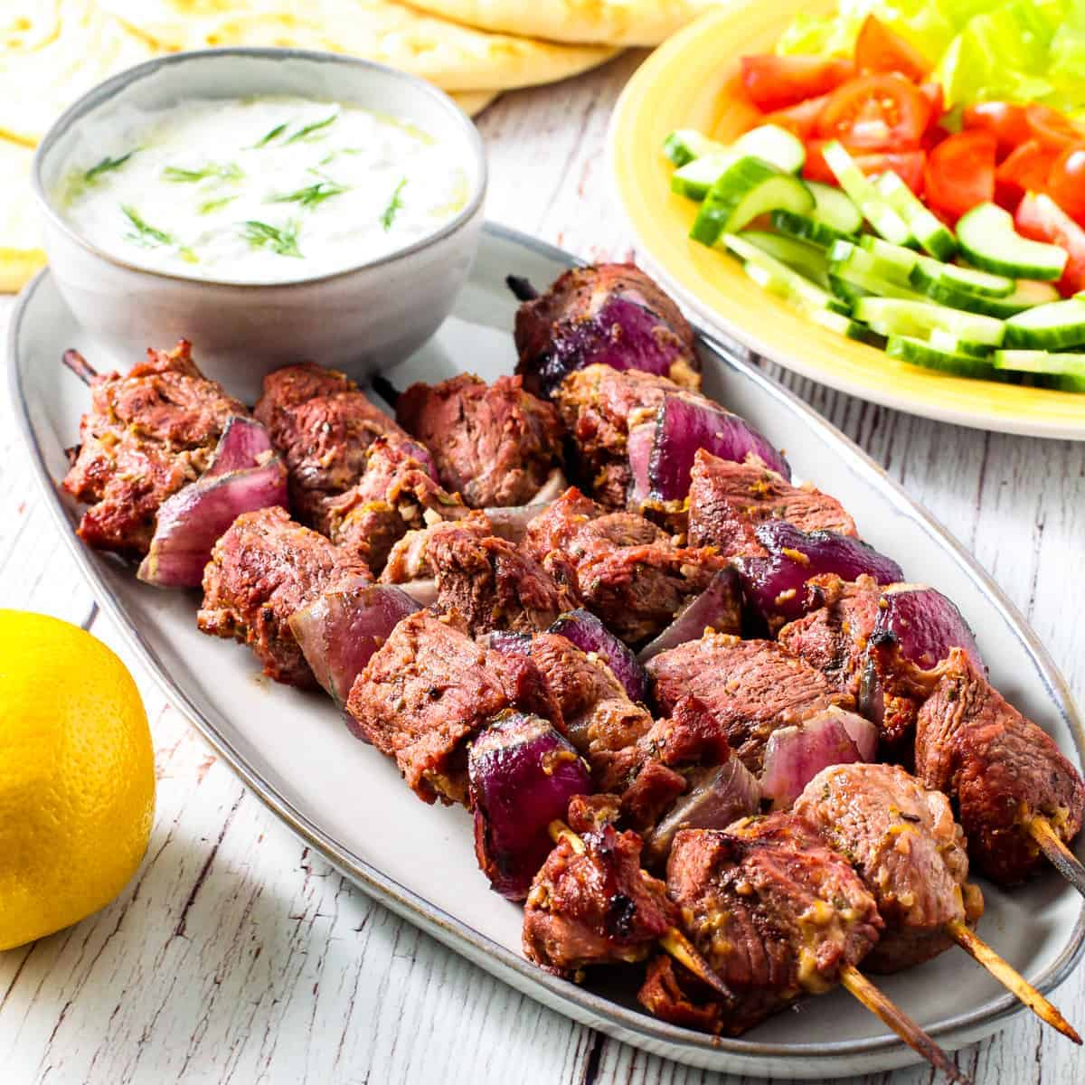 Greek yogurt marinated lamb kebabs shown served on a platter with a bowl of tzatziki sauce,warm pita bread, and a platter of fresh vegetables.