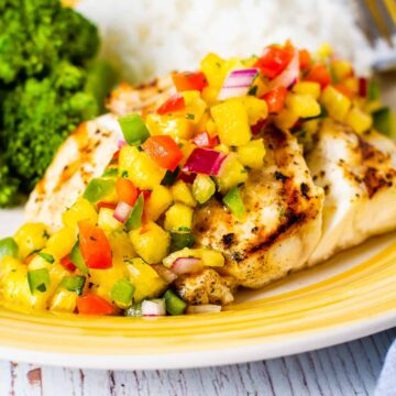 Grilled red snapper shown on a yellow dish topped with fresh pineapple salsa.