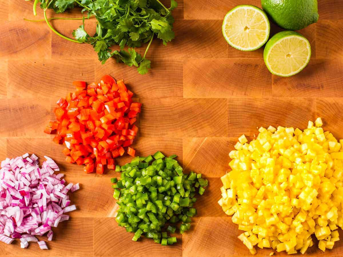 Ingredients for pineapple salsa shown in piles on a wooden cutting board.