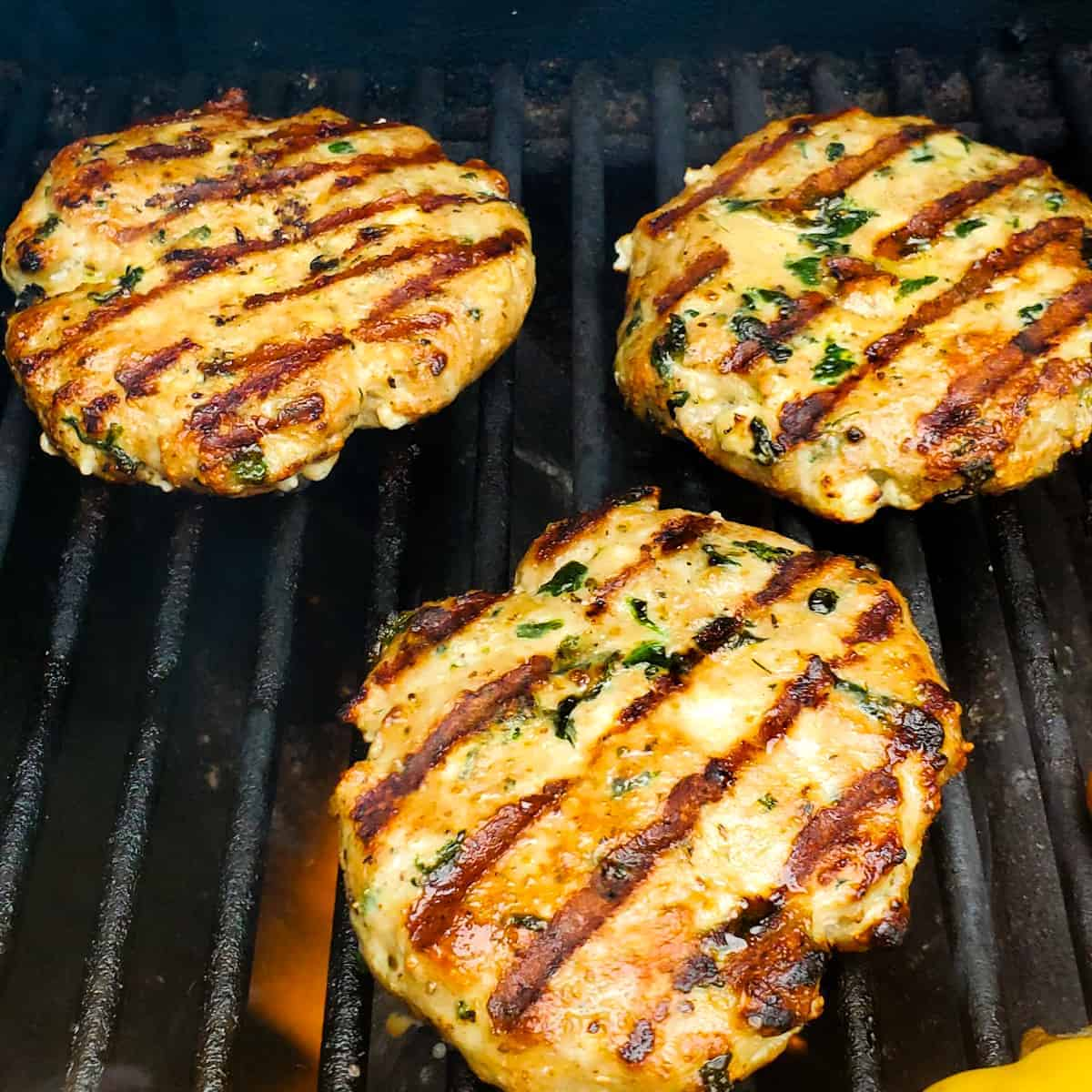 Turkey burgers with spinach and feta on the grill