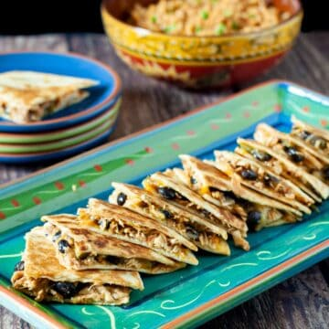 Chicken and black bean quesadillas shown sliced into wedges and served on a platter.