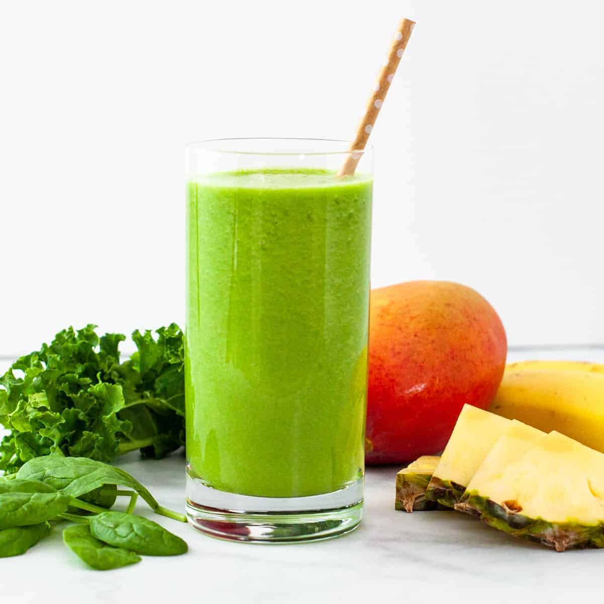 Tropical green smoothie in a glass, surrounded by fresh fruits and greens