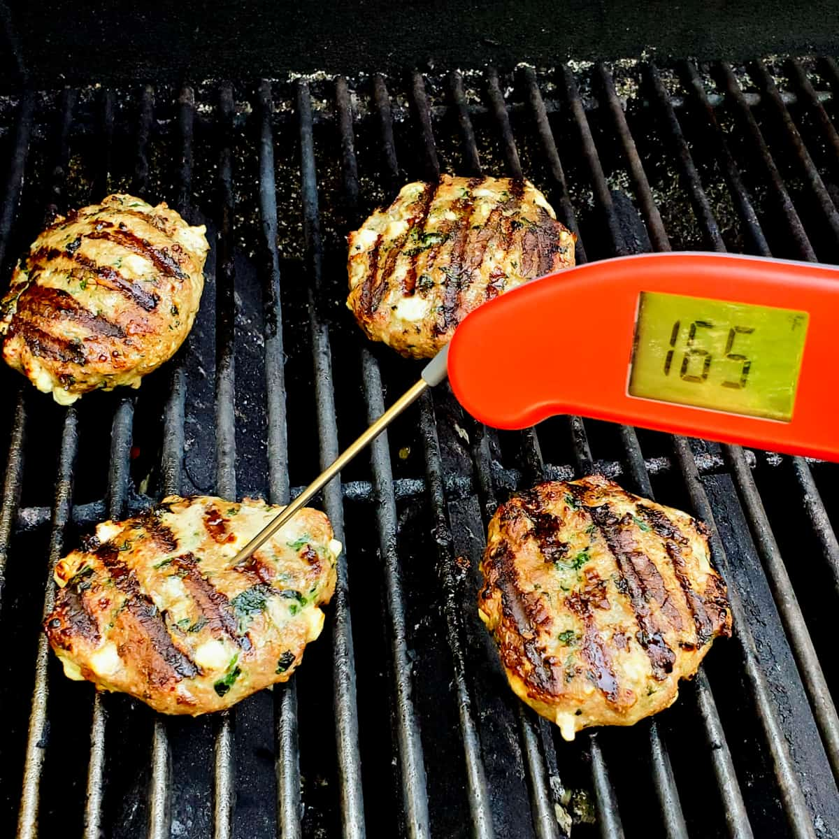 Cooked turkey burgers on the grill with a thermometer instered showing a final temperature of 165 degrees.