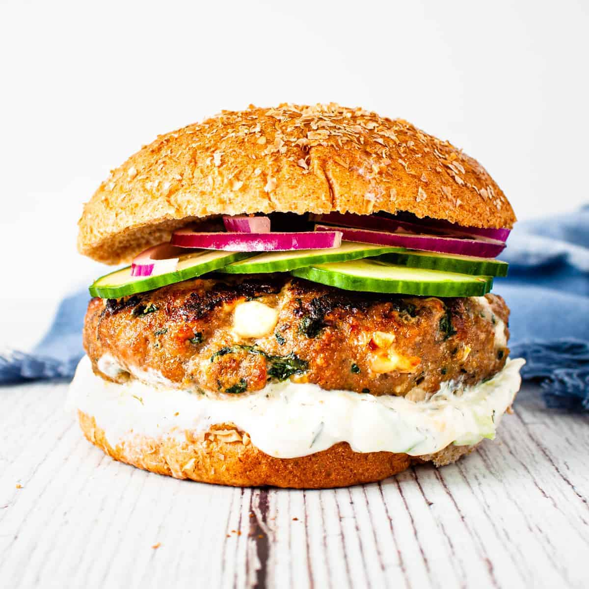 Close up image of a spinach and feta turkey burger on a wheat bun with a thick spread of tzatziki sauce and topped with sliced cucumber and red onion.